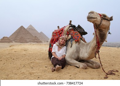 female tourist with camel sitting in front of the pyramids frog perspective