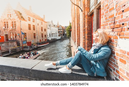 A female tourist in casual clothes and a blue jacket sits on a bridge near the river in Bruges in the spring and looks at boats sailing past with tourists. Travel to Belgium