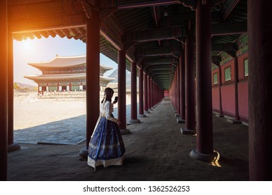Female tourist Dressed in traditional dress Hanbok walking at Gyeongbokgung palace, Seoul South Korea