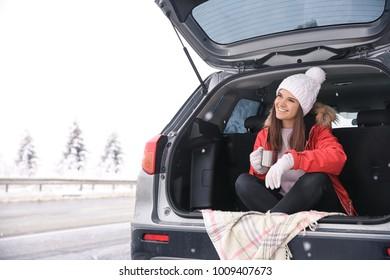 Female tourist drinking tea when sitting in car trunk