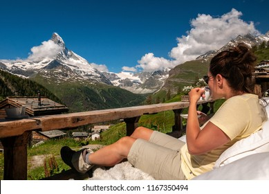 Female tourist enjoying morning coffee with a beautiful view of majestic Matterhorn. Visiting Valais alps and hiking around Zermatt.