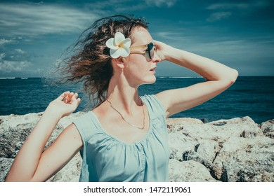 Female tourist enjoying sunny day on beach. Skincare sun protection concept. Girl enjoy freedom exotic alone vacation. People travel. Windr in wavy hair. Closeup portrait of beautiful woman on sea