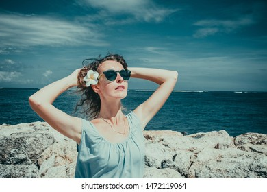 Female tourist enjoying sunny day on beach. Skincare sun protection concept. Girl enjoy freedom exotic alone vacation. People travel. Flower in wavy hair. Closeup portrait of beautiful woman on sea