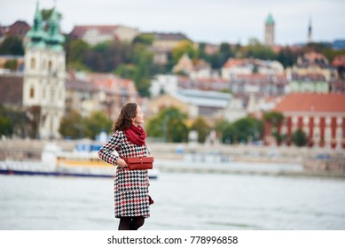 Female tourist is enjoying view of Buda side of Budapest with the Buda Castle, St. Matthias and Fisherman's Bastion. Background blurred. Her hair is blown by the wind