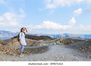 Female tourist enjoying view on Nea Kameni; volcanic island of Santorini on beautiful sunny day, Greece