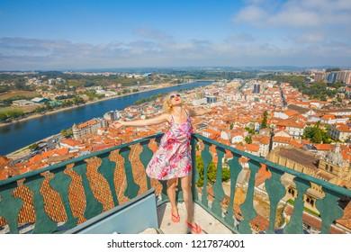 Female tourist enjoys in Portugal, Coimbra cityscape and Santa Clara Bridge on Mondego river. Caucasian tourist woman admiring Coimbra panorama sitting on top of bell Clock Tower.