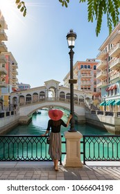 Female tourist enjoys the view to the Qanat Quartier on the Pearl in Doha, Qatar