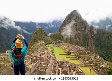 Female tourist gesturing a love sign to the famous ancient Inca ruins of Machu Picchu archaeological site, Cusco, Peru
