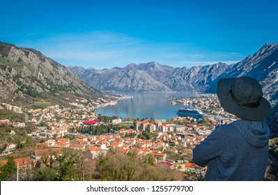 Female tourist with a hat admiring the stunning landscape of the Bay of Kotor in Montenegro as seen from the road to Lovcen National Park