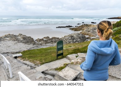 Female tourist hiking along Cliff Path coastal walk in Hermanus South Africa