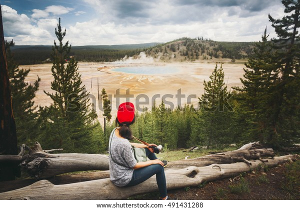 Female tourist is looking at a majestic view of Grand Prismatic Spring in Midway Geyser Basin geothermal area, part of Yellowstone National Park, Wyoming, USA. Vintage Tone.