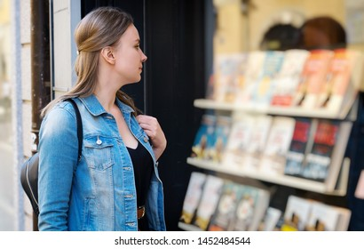 Female tourist looking at the shop window with books.