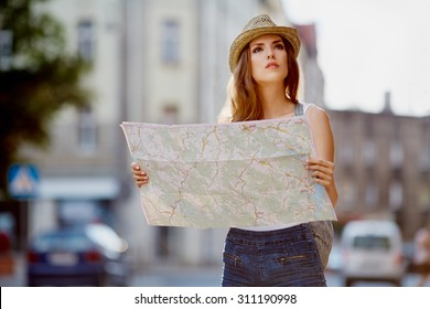 Female tourist with map visiting city and looking around