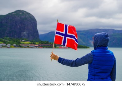 Female tourist with norwegian flag enjoying fjord Lysefjord view. National route Ryfylke. Vacation and travel.
