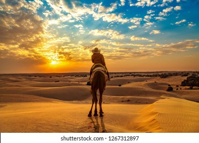 Female tourist on camel safari at the Thar desert Jaisalmer Rajasthan at sunset with moody sky.