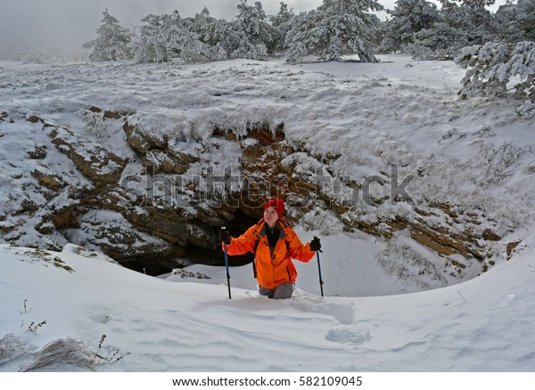 Female tourist in orange coat walking through the snow in the mountains