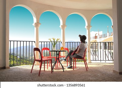 Female tourist with pamela, in a typical viewpoint of Frigiliana, Malaga,with white arches and turquoise blue sky,  observing the landscape while drinking sitting on the terrace of a bar a jug of beer