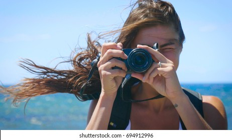 A female tourist photographer is taking pictures, with a backpack on her back, a wonderfully beautiful view of the blue sea and sky. Concept: travel, vacation, photo camera, photo courses, lifestyle.