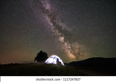 Female tourist resting at night camping in the mountains under incredible beautiful starry sky and Milky way. Woman sitting inside illuminated tent and looking at sky full of stars. Astrophotography