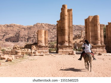 Female tourist riding a donkey with a drover in front of her among the ruins of Petra