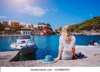 Female tourist sitting on the pier with blau sun hat laying behind. Assos village with beautiful traditional houses is in front of sea bay. Kefalonia, Greece