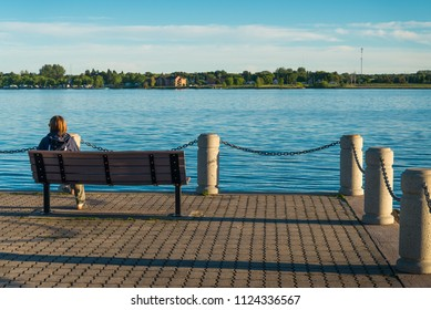 Female tourist sitting at the shore of St. Mary's River in Sault Ste Marie in Ontario and watching the US side across the river
