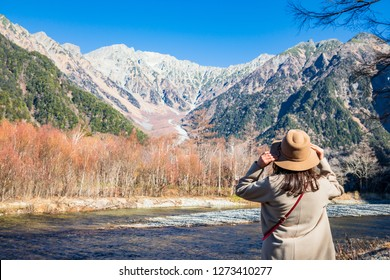 Female tourist standing on the Azusa river at Kamikochi, the northern part of the Japan Alps. Beautiful scenery .There are many natural and adventure hiking trails at Nagano Prefecture,Japan