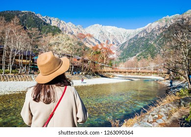 Female tourist standing on the kappa wooden bridge at Kamikochi, the northern part of the Japan Alps. Beautiful scenery .There are many natural and adventure hiking trails at Nagano Prefecture,Japan