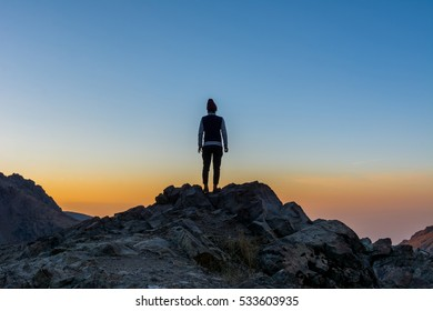 A female tourist standing on the peak of a rocky mountain watching sun rising in Darband valley in autumn in dawn against colorful sky in the Tochal mountain.