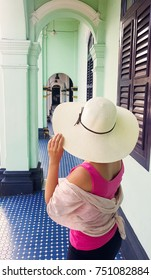 Female tourist with straw hat in streets of Phuket town