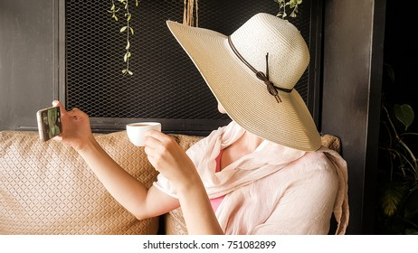 Female tourist with straw hat taking selfie in Phuket town