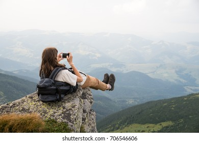 Female tourist takes photo of legs with cell phone from top of the mountain cliff. Hiker girl with backpack taking self portrait in beautiful scenery on a rock in ukrainian carpathians