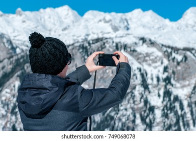 Female tourist taking panoramic picture of beautiful winter mountain landscape with compact digital camera