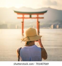 Female tourist taking photo of the floating Torii gate in Miyajima island, Japan