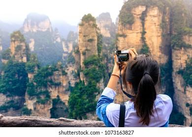 female tourist taking photo at hallelujah mountain in Zhangjiajie national forest park,hunan,china