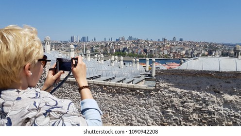 Female tourist taking a photo of Istanbul over Golden Horn