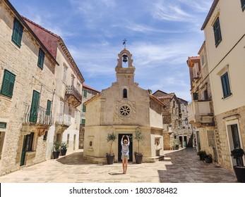 Female tourist taking photo of mall church on square of small urban village of Stari grad on Hvar island in Croatia, Adriatic Sea, Europe. - Shutterstock ID 1803788482