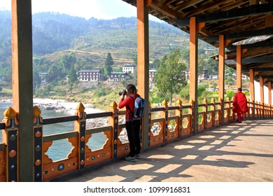 Female tourist taking photograph at PUNA MOCCHU BAZAM : Antique  wooden bridge at Punakha Dzong Monastery or Pungthang Dewachen Phodrang  Bhutan