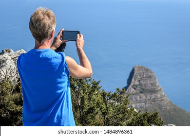 Female tourist taking photos of Lions head landmark Cape Town South Africa from vantage point of Table mountain with Blue sea in background.