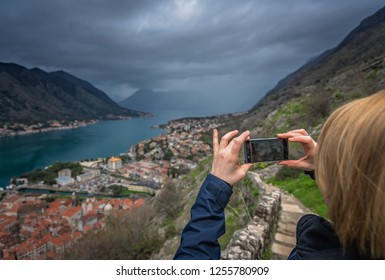 Female tourist taking pictures on her smartphone of a stunning landscape of the Bay of Kotor, during cloudy stormy day, Montenegro