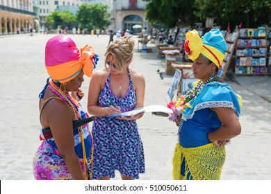 Female tourist talking with two Cuban women in traditional clothing on the Havana street