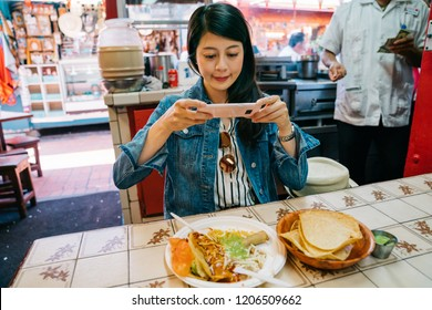 female tourist trying the traditional taco in the market and let the phone eat first. young girl independent travel in USA. traveler recording the Mexican food in her holiday trip.