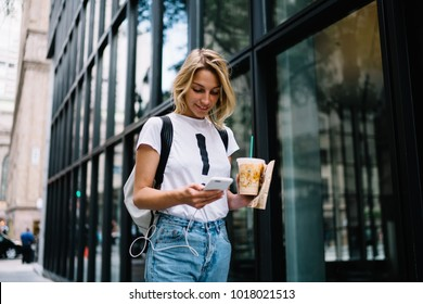 Female tourist using information from travel blogs browsed on mobile phone walking in city street, hipster girl navigating via application on smartphone walking with take away beverage coffee outdoors