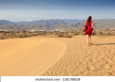 Female tourist visits Gran Canaria sand dunes - Maspalomas desert landscape.