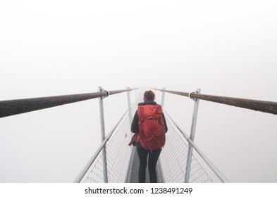 Female tourist walking across a suspension bridge into heavy fog