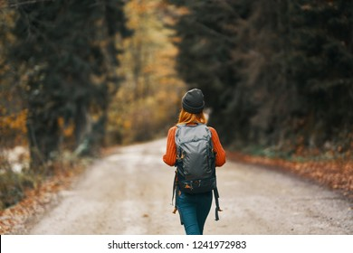 female tourist walking along a forest road