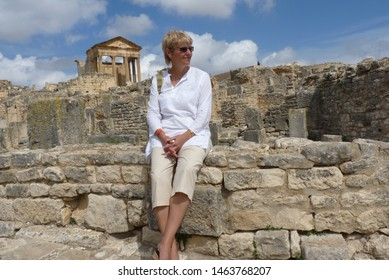 A female tourist in a white blouse and light breeches sits on the stones of the ruins of the ancient city against the blue sky and the Ancient Temple of Minerva. Summer day. Dougga Tunisia