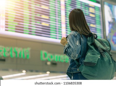 Female tourists  looking at the flight information board  in international airport.