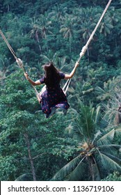 Female tourists swinging on beautiful natural place in Ubud, Bali, Indonesia.