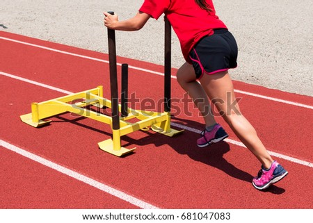 Female Track Field Athlete Pushing Yellow Stock Photo (Edit Now